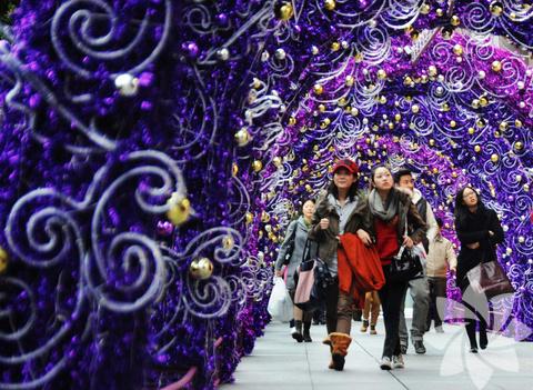 Çin: Şangay'da bulunan West Nanjing caddesinde kaldırıma kurulan yılbaşı dekorunun altından yürüyor.
