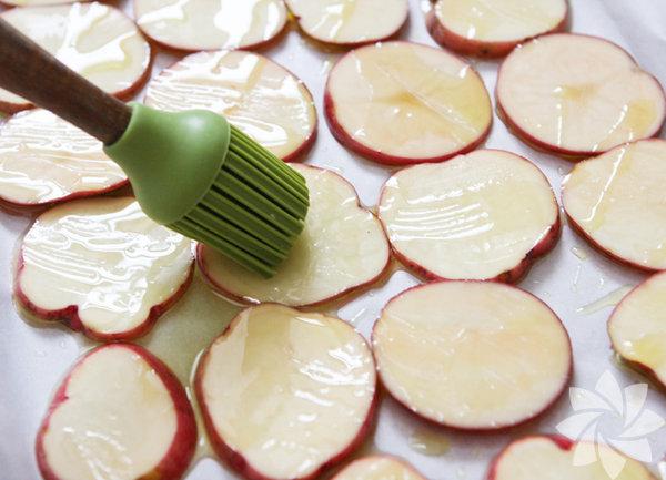 Patatesleri ince ince dilimliyoruz. Tarifte kırmızı patates kullanılmış. Fakat siz taze patates kullanabilirsiniz. Üzerine zeytinyağı sürdüğünüz patatesleri önceden ısıtılmış fırına veriyoruz.